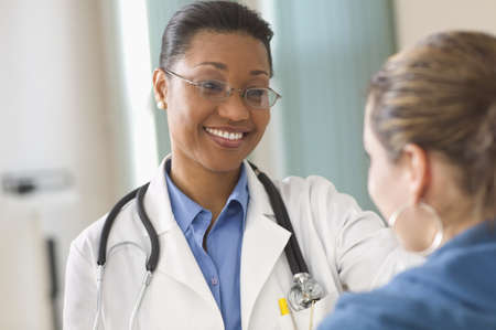 Woman doctor smiling while talking to patient LANG_EVOIMAGES