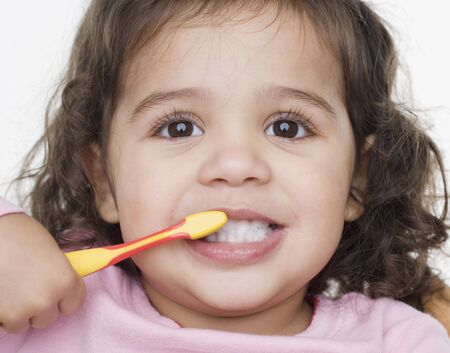 Close up portrait of little girl brushing teeth LANG_EVOIMAGES