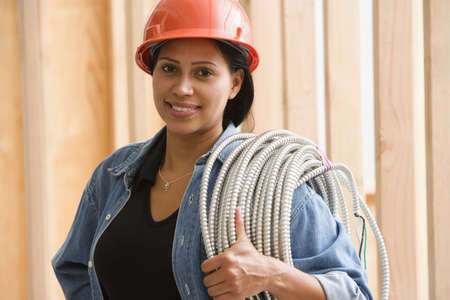 Portrait of female construction worker carrying wiring on shoulder