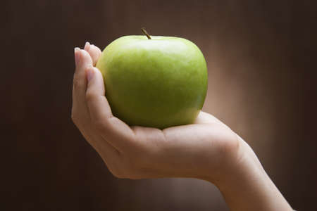 Woman holding apple LANG_EVOIMAGES