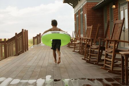 Young boy wearing inner tube on wooden deck LANG_EVOIMAGES