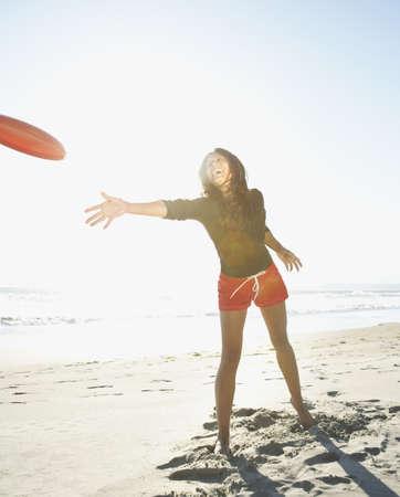 Woman throwing frisbee on beach