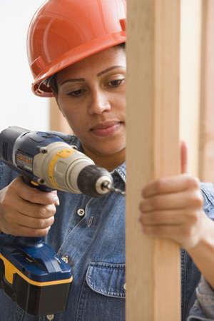 Female construction worker drilling into framing