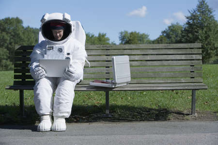 Astronaut examining a folder on a bench LANG_EVOIMAGES