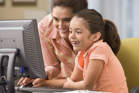 Mother helping daughter with computer