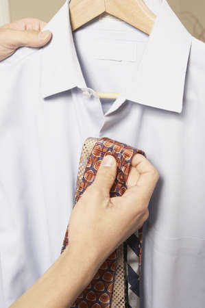 Man holding two ties up to a collared shirt, San Rafael, California, United States LANG_EVOIMAGES