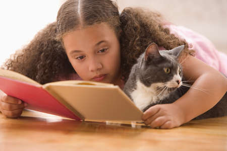 Girl laying reading book with cat