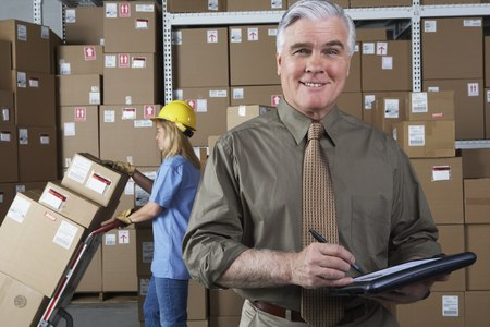 Businessman in warehouse with clipboard