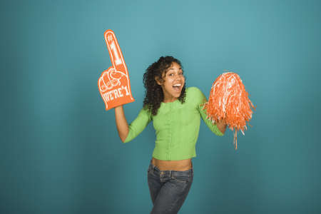 Young woman with a foam hand and cheerleading pompom LANG_EVOIMAGES