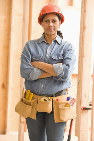 Portrait of female construction worker wearing tool belt and hard hat LANG_EVOIMAGES