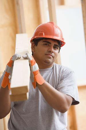 Portrait of construction worker carrying 2x4ís on shoulder