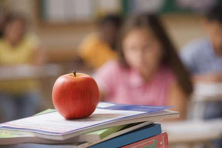 Apple resting on schoolbooks LANG_EVOIMAGES