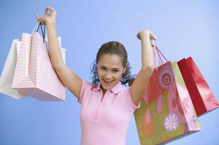 Portrait of teenage girl holding gift bags