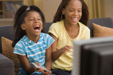 Sisters laughing at the television