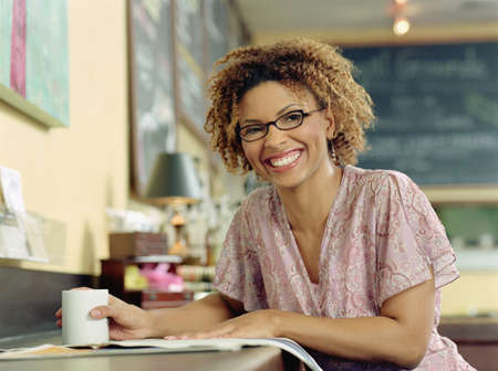 Businesswoman smiling for the camera with cup of coffee