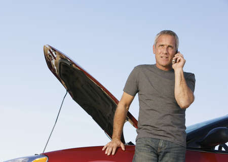 Mature man on cell phone with car breakdown