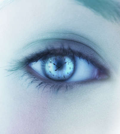 Close-up of a young womans eye reflecting a clock LANG_EVOIMAGES
