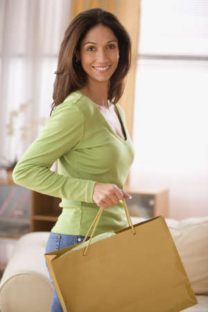 Young woman holding a shopping bag LANG_EVOIMAGES