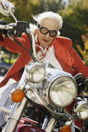 Elderly woman driving a motorcycle LANG_EVOIMAGES