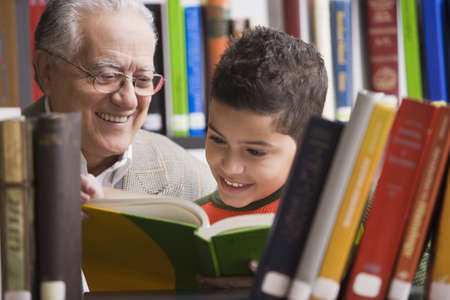 Young boy and grandfather reading in library