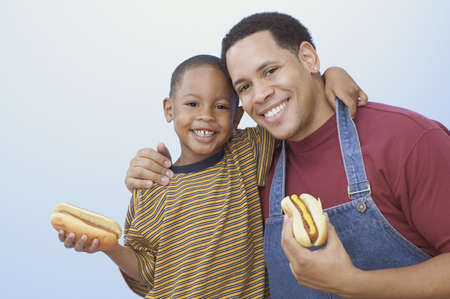 Father and son hugging while holding hot dogs