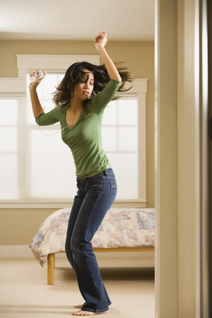 Woman dancing in bedroom while listening to music LANG_EVOIMAGES