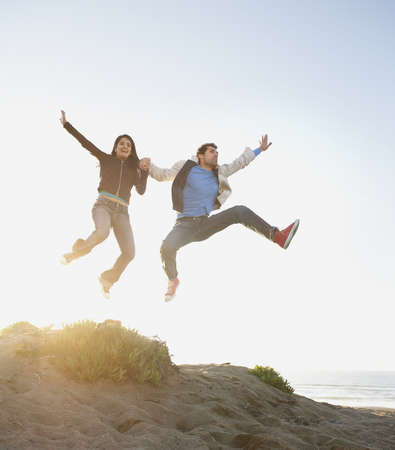 Portrait of young couple jumping on beach
