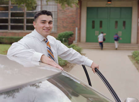 Young businessman smiling for the camera by his car
