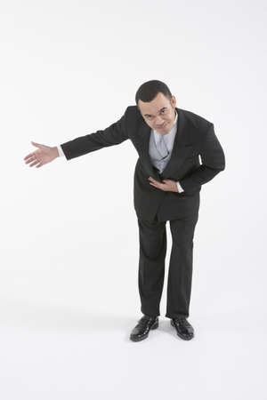 Asian butler bowing and making a welcoming gesture