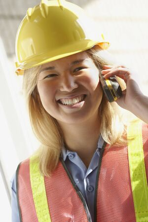 Female construction worker on cell phone LANG_EVOIMAGES