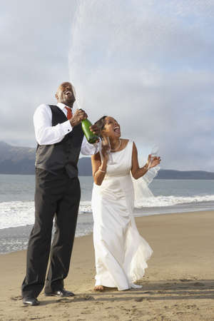 Newlyweds opening champagne bottles LANG_EVOIMAGES