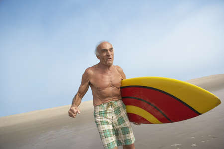 Senior man with surfboard at the beach, Las Vegas, Nevada, United States