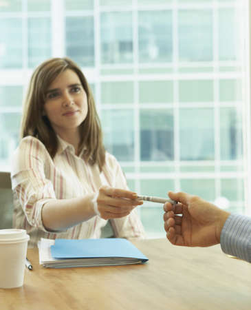 Businesswoman handing a pen to a businessman, Redwood City, California, United States