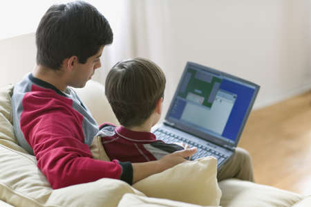 High angle view of father and son on couch with laptop LANG_EVOIMAGES