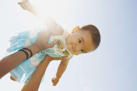 Woman holding her baby in the air LANG_EVOIMAGES