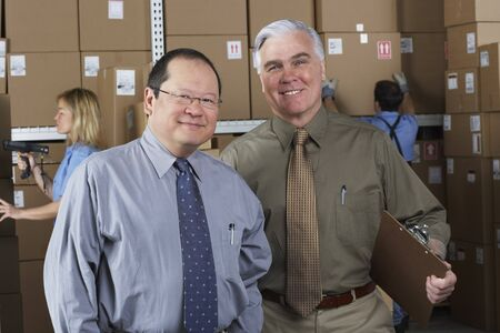 Two businessmen in warehouse LANG_EVOIMAGES