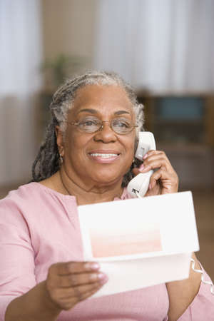 Portrait of senior adult woman holding up papers while on phone LANG_EVOIMAGES