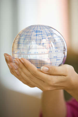 Woman holding a plastic globe LANG_EVOIMAGES