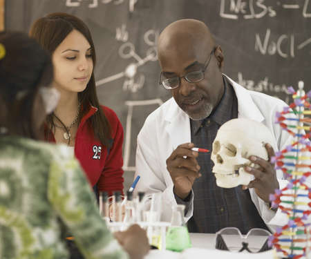 African male science teacher showing students a human skull, Toronto, Canada LANG_EVOIMAGES