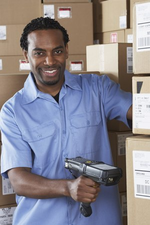 Male African warehouse worker scanning packages LANG_EVOIMAGES