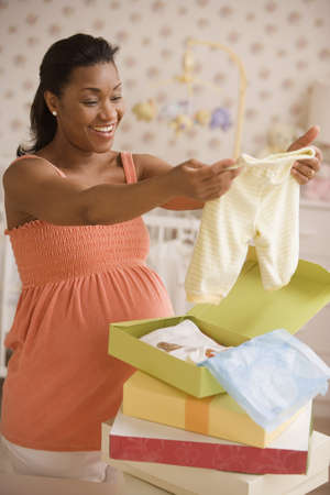 Pregnant African mother opening gifts of baby clothes LANG_EVOIMAGES