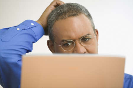 Close up of mature man with laptop scratching head LANG_EVOIMAGES