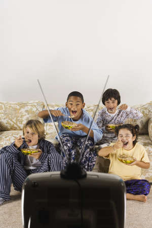Group of children eating and watching television