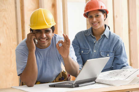 Portrait of two construction workers gesturing okay while talking on cell phone