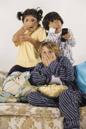 Group of children eating popcorn and watching a scary movie LANG_EVOIMAGES