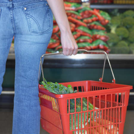 Close up of woman holding grocery basket at supermarket, Perth, Australia