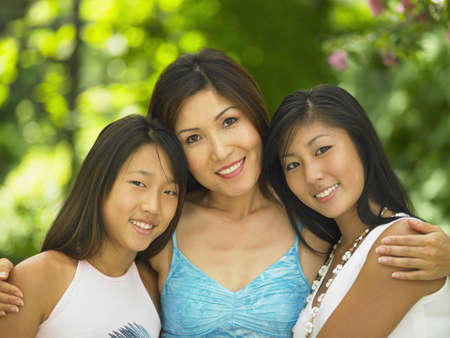 Portrait of mother hugging daughters LANG_EVOIMAGES