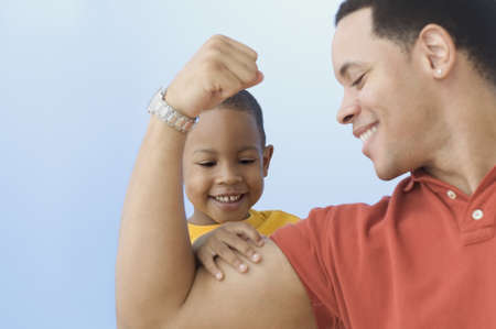 Father flexing muscle for young son