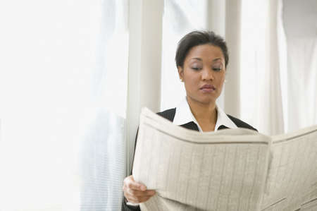 African American businesswoman reading newspaper LANG_EVOIMAGES
