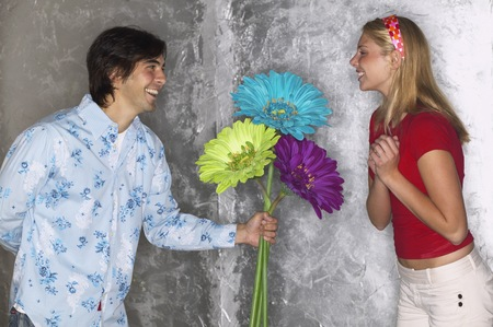 Young man giving young woman large flowers LANG_EVOIMAGES